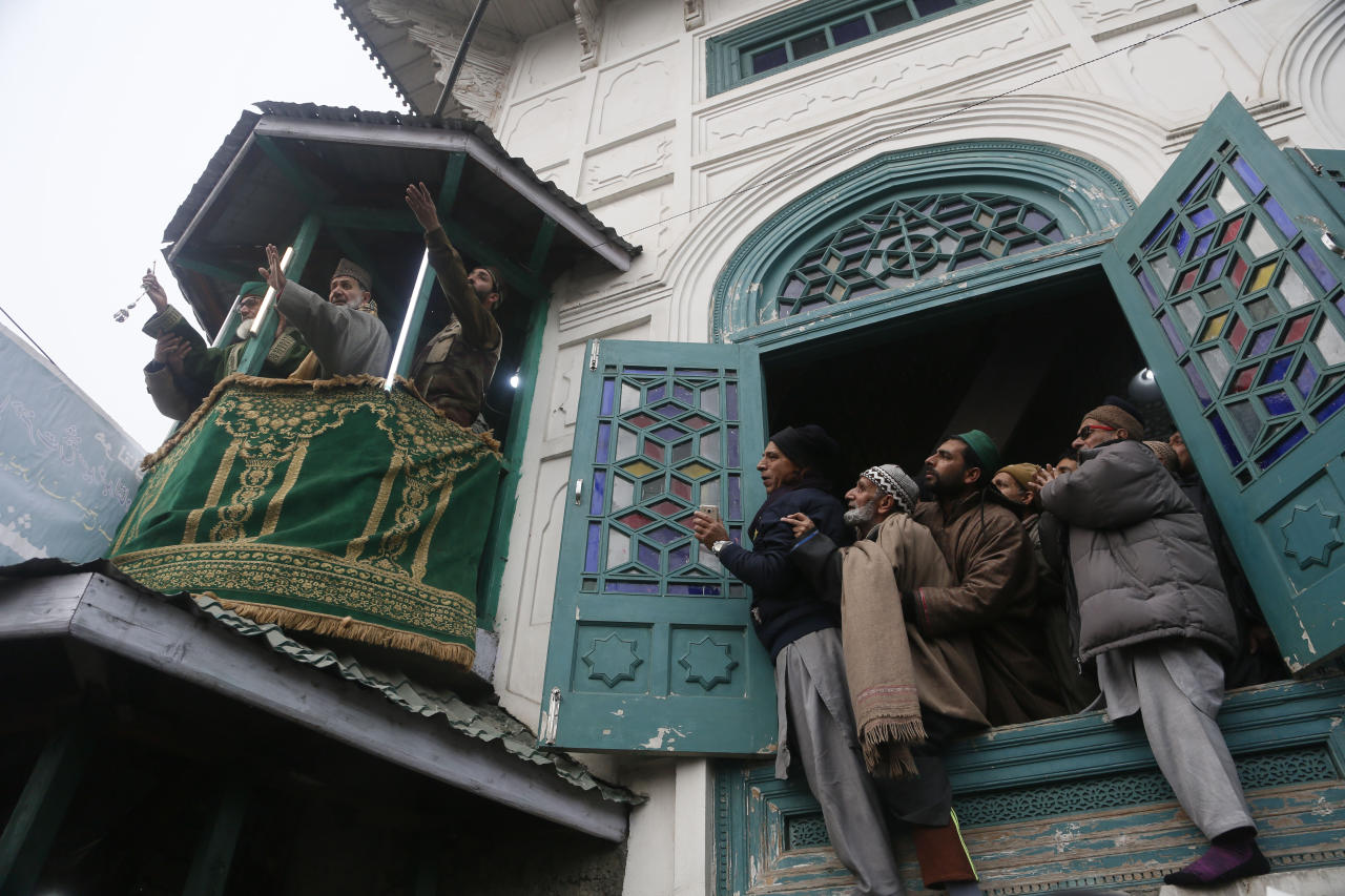 Kashmiri Muslim devotees pray as a priest displays a relic of Sufi saint Sheikh Syed Abdul Qadir Jeelani outside his shrine in Srinagar, Indian controlled Kashmir, Monday, Dec. 9, 2019. Hundreds of devotees have gathered at the shrine for the 11-day festival that marks the death anniversary of the Sufi saint. (AP Photo/Mukhtar Khan)