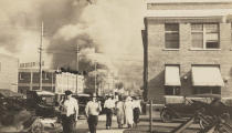 In this photo provided by Department of Special Collections, McFarlin Library, The University of Tulsa, two armed men in walk away from burning buildings as others walk in the opposite direction during the June 1, 1921, Tulsa Race Massacre in Tulsa, Okla. (Department of Special Collections, McFarlin Library, The University of Tulsa via AP)