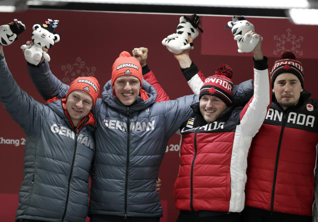 Germany and Canada celebrate gold in the two-man bobsled final at the 2018 Winter Olympics in Pyeongchang, South Korea. (AP)