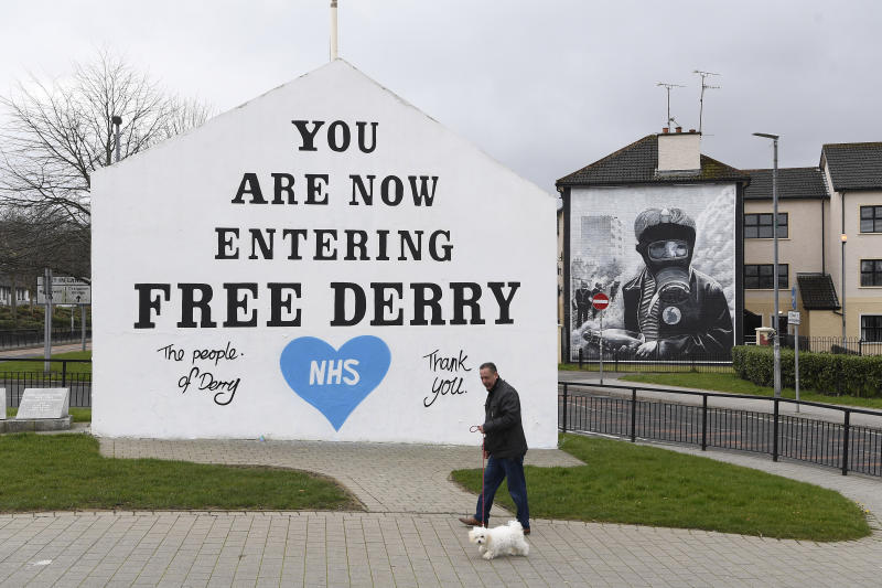 A man walks his dog past a message of support for the NHS on the Free Derry Corner wall in Londonderry, as the UK continues in lockdown to help curb the spread of the coronavirus. (Photo by Michael Cooper/PA Images via Getty Images)