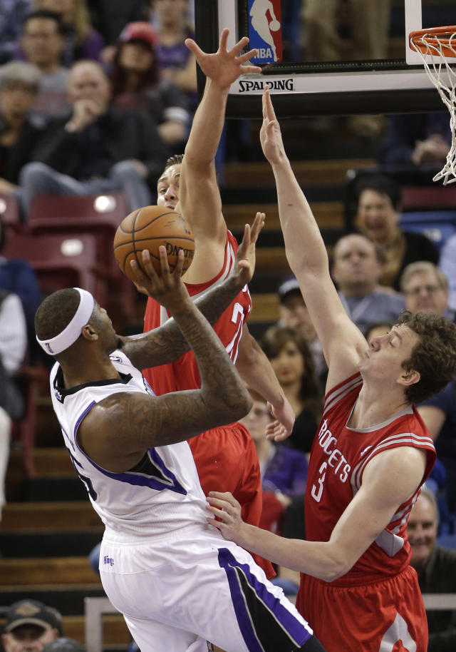 Sacramento Kings center DeMarcus Cousins, left, goes to the basket against Houston Rockets' Donatas Motiejunas, of Lithuania, center, and Omer Asik of Turkey, during the first quarter of an NBA basketball game in Sacramento, Calif., Tuesday Feb. 25, 2014.(AP Photo/Rich Pedroncelli)