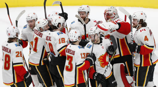 Calgary Flames goaltender Mike Smith (41) celebrates 5-3 win against the San Jose Sharks with teammates in the third period of an NHL hockey game in San Jose, Calif., Sunday, March 31, 2019. (AP Photo/Josie Lepe)