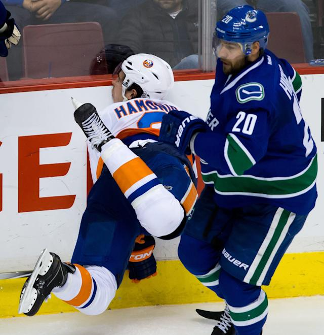 New York Islanders' Travis Hamonic, left, is checked into the boards by Vancouver Canucks' Ryan Kesler as Chris Higgins, right, skates past during third period NHL hockey action in Vancouver, British Columbia, on Monday March 10, 2014. (AP Photo/The Canadian Press, Darryl Dyck)