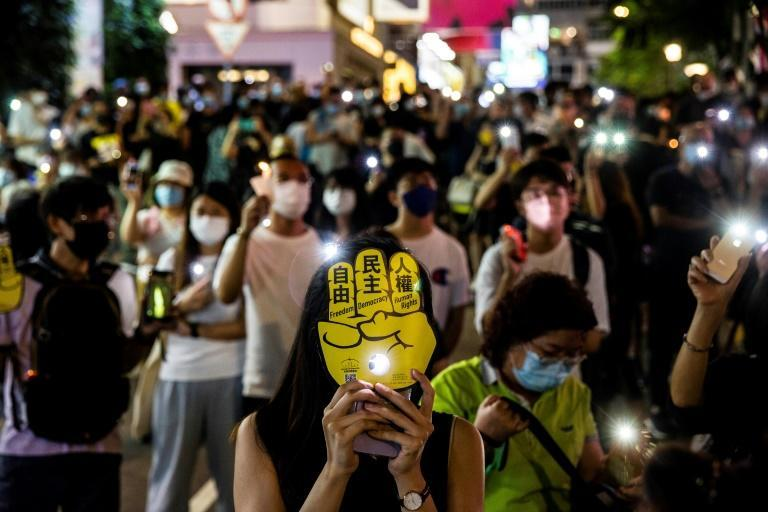 People hold up their phones with the light on in Hong Kong in remembrance of China's Tiananmen Square crackdown