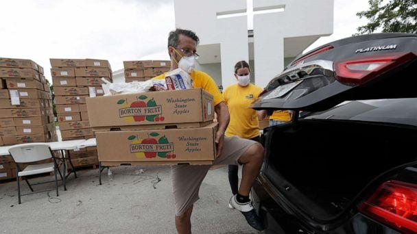 PHOTO: Oscar Amuz, with Volunteers in Action, loads groceries into cars during a food distribution event, July 21, 2020, at St. Monica's Catholic Church in Miami Gardens, Fla. (Wilfredo Lee/AP)