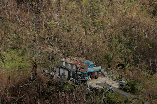 <p>A woman stands on the porch of her damaged home as recovery efforts continue following Hurricane Maria near Orocovis, Puerto Rico, Oct. 7, 2017. (Photo: Lucas Jackson/Reuters) </p>