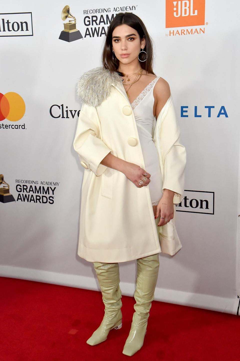 <p>Dua wearing a sexy slip dress under a cream coat pared with vinyl knee-length boots at a pre-Grammys gala.</p>