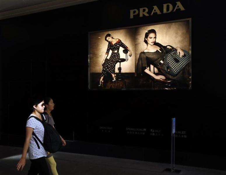 Shoppers walk past a Prada store at Hong Kong's shopping Tsim Sha Tsui district September 16, 2013, one day before the Hong Kong-listed Italian fashion label announces its 2013 first-half results in the territory. REUTERS/Bobby Yip