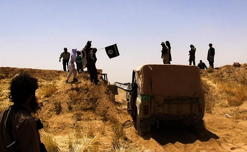 An image provided by Al-Baraka News allegedly shows jihadist militants celebrating as they drive across the Iraq-Syria border on June 9, 2014