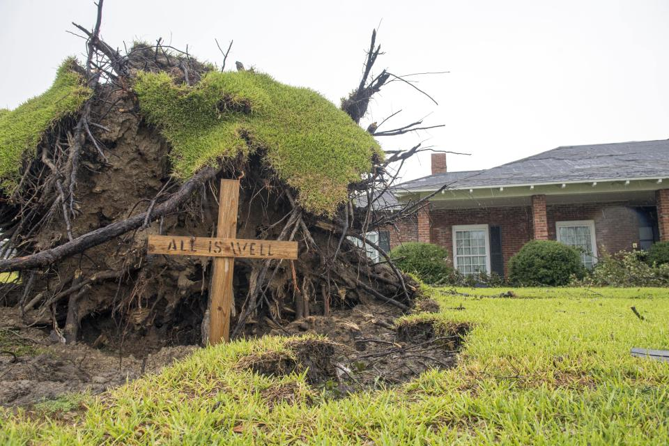 A wooden cross where a pine tree fell just missing this house by inches is seen following Hurricane Laura Friday, Aug. 28, 2020 in Lake Charles, La. (Chris Granger/The Times-Picayune/The New Orleans Advocate Via AP)