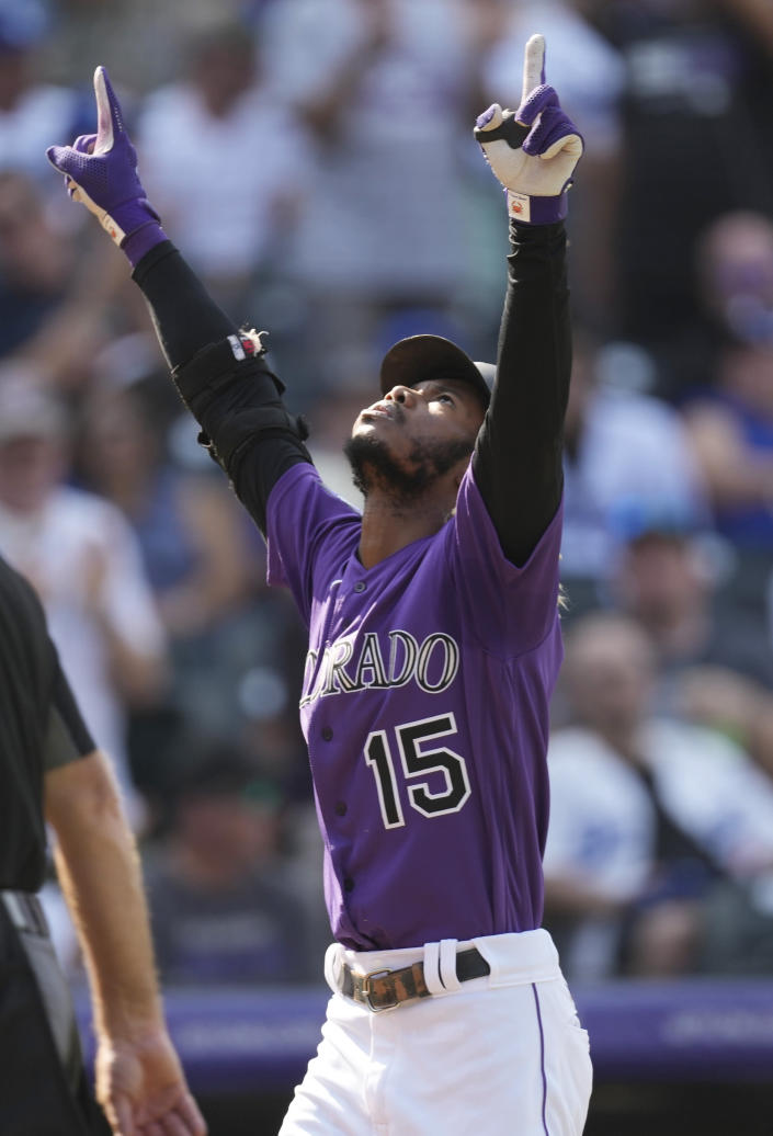 Colorado Rockies' Raimel Tapia gestures as he crosses home plate after hitting a two-run home run off Los Angeles Dodgers starting pitcher Max Scherzer in the fifth inning of a baseball game Thursday, Sept. 23, 2021, in Denver. (AP Photo/David Zalubowski)
