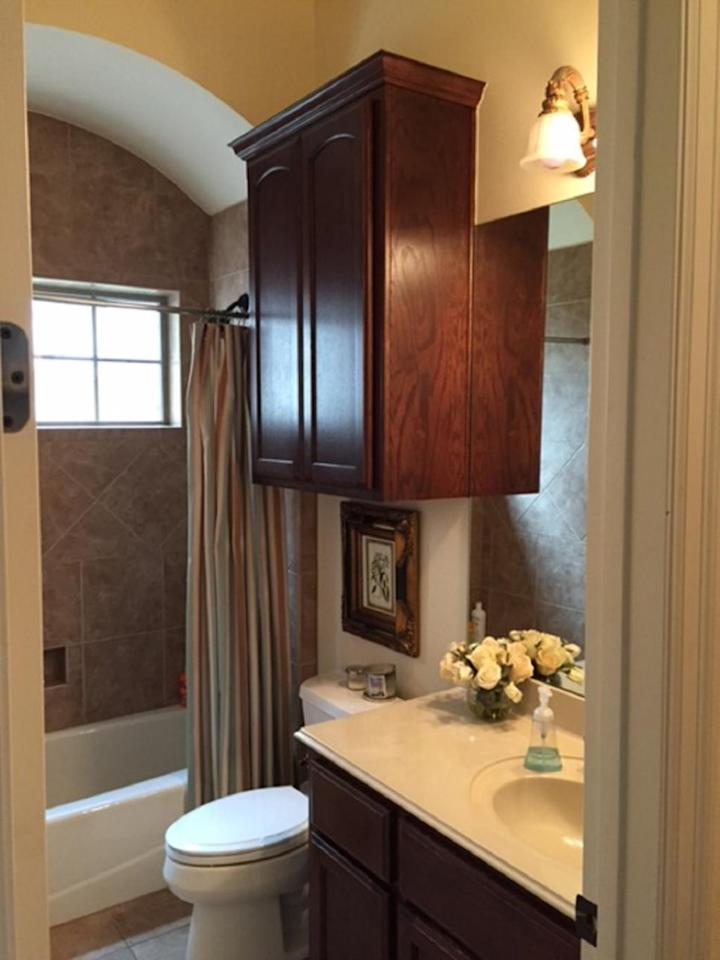 <p>With dark wood cabinets and dull, colorless tiles, this guest bathroom is anything but inviting.</p>