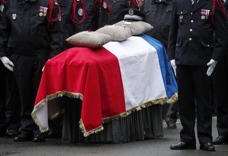 Medals are pictured on a coffin one of the four victims of last week's knife attack during a ceremony in the courtyard of the Paris police headquarters Tuesday, Oct. 8, 2019 in Paris. France's presidency says the four victims of last week's knife attack at the Paris police headquarters will be posthumously given France's highest award, the Legion of Honor. (AP Photo/Francois Mori)