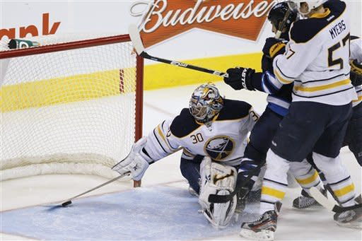 Buffalo Sabres goaltender Ryan Miller (30) gets his stick on a Winnipeg Jets shot as Jets' Tanner Glass (15) and Sabres' Tyler Myers (57) fight for position during first-period NHL hockey game action in Winnipeg, Manitoba, Thursday, Jan. 19, 2012. (AP Photo/The Canadian Press, John Woods)