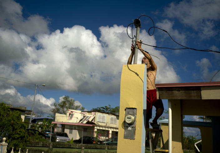 FILE - In this Oct. 13, 2017 file photo, a resident tries to connect electrical lines downed by Hurricane Maria in preparation for when electricity is restored in Toa Baja, Puerto Rico. Researchers said on April 22, 2021, they are launching a survey of the causes of deaths following the Category 4 storm to clear up questions about a death toll that analysts so far have attributed to factors such as power outages, building failures, and damaged roads. (AP Photo/Ramon Espinosa, File)