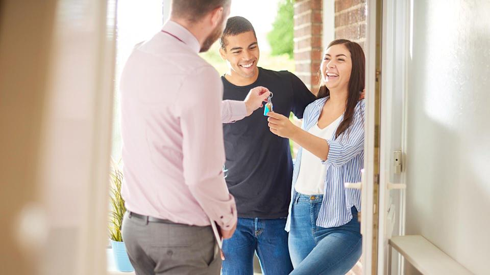 a young couple view a property guided by an estate agent.