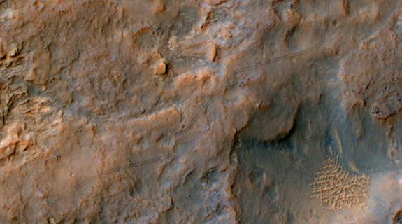 Two parallel tracks left by the- wheels of NASA's Curiosity Mars rover cross rugged ground in this portion of a Dec. 11, 2013, observation by the High Resolution Imaging Science Experiment (HiRISE) camera on NASA's Mars Reconnaissance Orbiter.