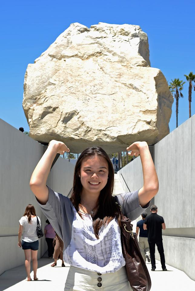 LOS ANGELES, CA - JUNE 26:  Telena Vo poses with the new art exhibit  ''Levitated Mass,'' a permanent exhibit at the Los Angeles County Museum of Art in California on June 26, 2012 in Los Angeles, California. The exhibit was created by artist Michael Heizer, which features a 340-ton megalith rock.  (Photo by Kevork Djansezian/Getty Images)