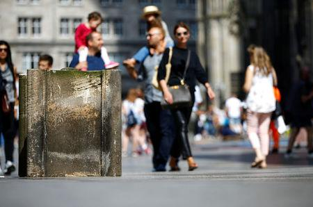 People walk past concrete barriers placed by police in front of the world famous gothic cathedral in Cologne