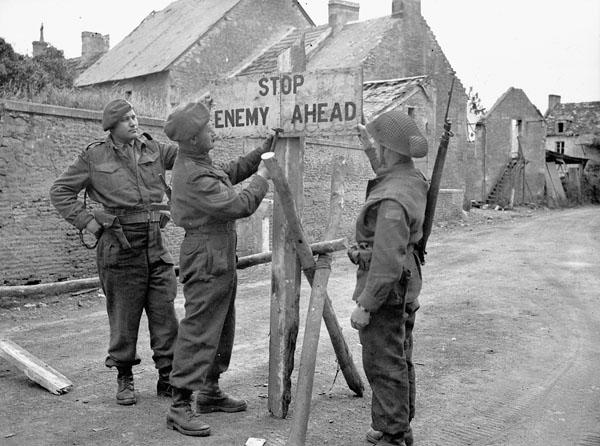 <p>Photographer: Dubervill, Frank L.<br /> Location: Bretteville-le-Rabet, France:<br /> Description: Sgt. T.S. Giles (Winnipeg, MB)(centre) and Lt. Howard Germen (Drumheller, AB) (holding sign in place)<br /> Credit: Library and Archives Canada </p>