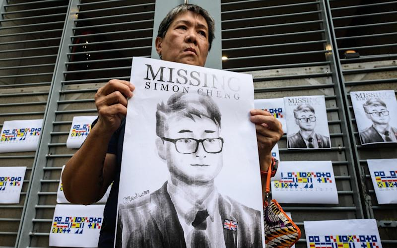 An activist holds up a sign with Mr Cheng's face after his disappearance last August - AFP/AFP Contributor#AFP