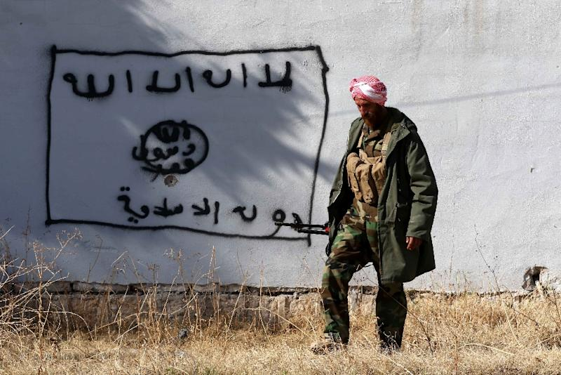 A Kurdish fighter walks by a wall bearing a drawing of the flag of the Islamic State group in the northern Iraqi town of Sinjar, on November 13, 2015 (AFP Photo/Safin Hamed)