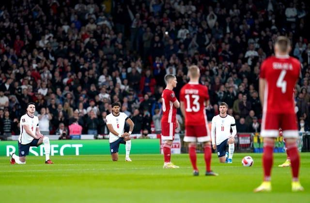 Tyrone Mings, centre, and England take a knee while Hungary remain standing