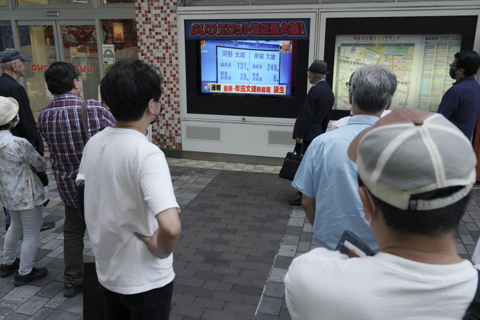 """Pedestrians look at a public TV showing the results of the Liberal Democratic Party's presidential election Wednesday, Sept. 29, 2021, in Tokyo. Former Foreign Minister Fumio Kishida has won the governing party leadership election and is set to become the next prime minister. The Japanese letters read: """"Fumio Kishida new LDP president."""" (AP Photo/Eugene Hoshiko)"""