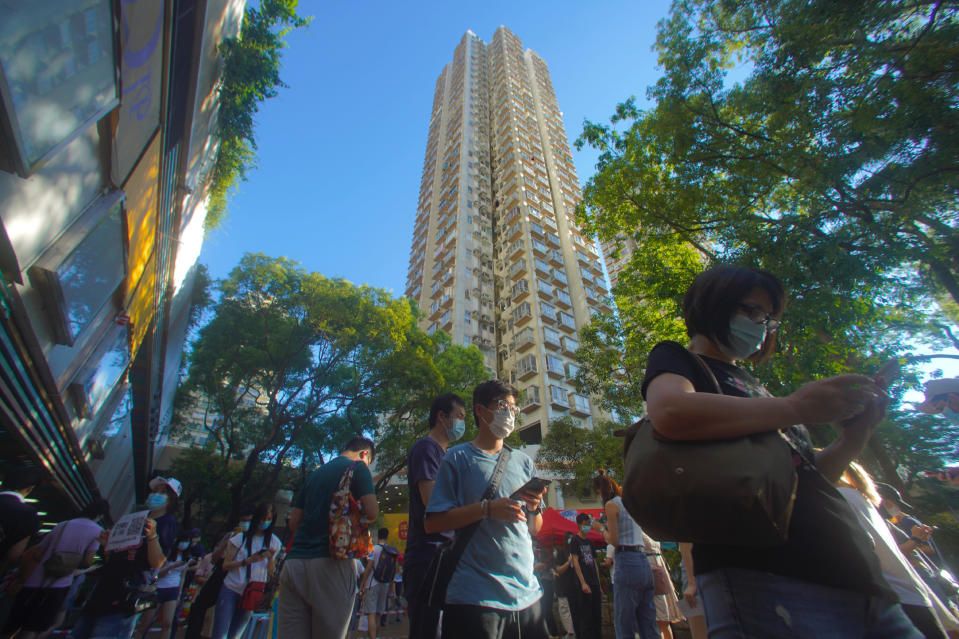 People queue up to vote in Hong Kong Sunday, July 12, 2020, in an unofficial primary for pro-democracy candidates ahead of legislative elections in September. Over 200,000 Hong Kongers voted in an unofficial Hong Kong primary that will help the pro-democracy camp decide which candidates to field in legislative elections in September. The turnout exceeded organizers' estimates that some 170,000 people would turn up to vote over the weekend. (AP Photo/Vincent Yu)
