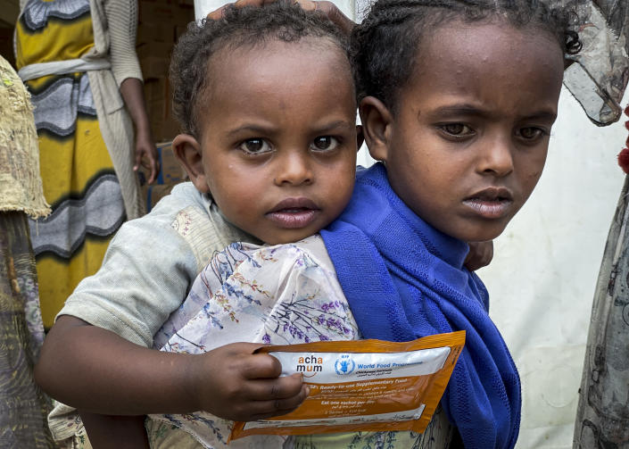 """Children who are either suffering from or at risk of malnourishment receive nutrient supplements from the World Food Programme (WFP) in the Adi Daero district, the first time the community has received nutrition support, in the Tigray region of northern Ethiopia Saturday, Aug. 21, 2021. For months, the United Nations has warned of famine in Tigray and now internal documents and witness accounts reveal the first starvation deaths since Ethiopia's government in June imposed what the U.N. calls """"a de facto humanitarian aid blockade."""" (Claire Nevill/WFP via AP)"""