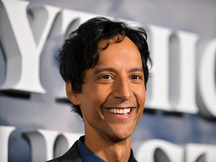 Danny Pudi smiles at a red carpet event.