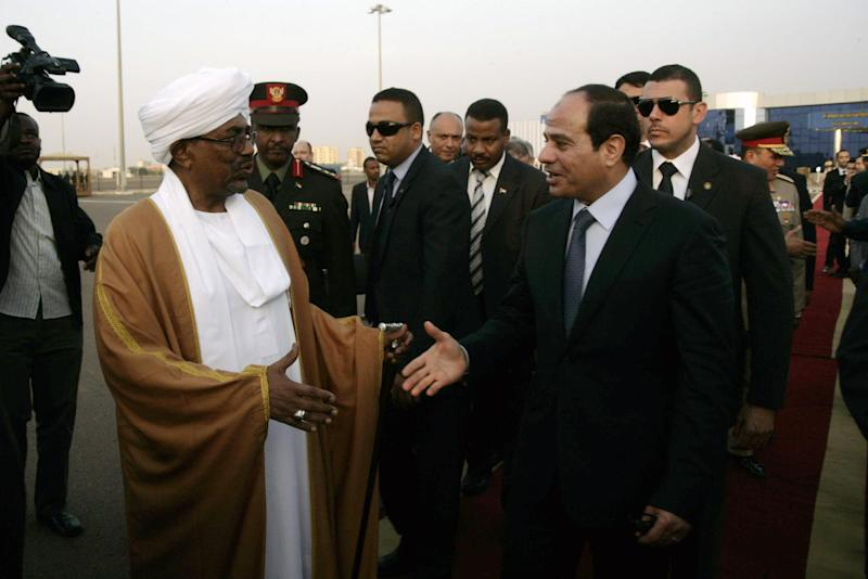 Omar al-Bashir (left) shakes hands with Abdel Fattah al-Sisi at Khartoum airport on June 27, 2014 after an official visit by the Egyptian President (AFP Photo/Ebrahim Hamid)
