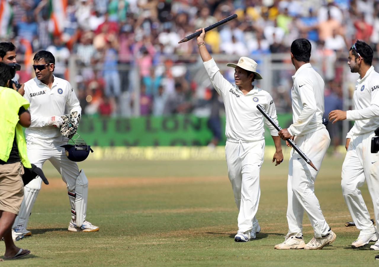 Cricket legend Sachin Tendulkar and other Indian cricketers celebrate after winning the Test match series against West Indies on the third day of the second Test to give a fitting farewell to Tendulkar in his farewell and 200th Test at the Wankhede Stadium in Mumbai on Nov.16, 2013. (Photo: IANS)