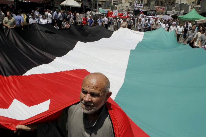 FILE - In a July 13, 2012 file photograph, a follower of the Jordanian Muslim Brotherhood movement carries a Jordanian flag during a protest in Amman, Jordan. The Muslim Brotherhood has announced it will boycott the upcoming elections in Jordan, saying reforms enacted by the King Abdullah II could loosen his loyalists' domination of the parliament and give the body somewhat greater authority do not go far enough. The palace says it won't go any further and insists the vote will go ahead even without the country's largest opposition group participating. (AP Photo/Raad Adayleh, File)