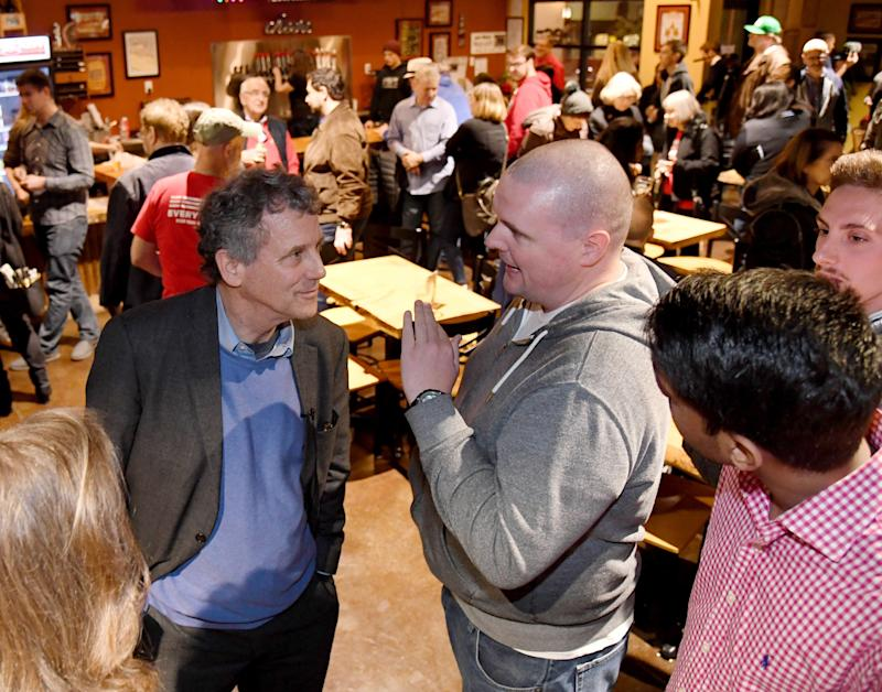 "Sen. Sherrod Brown (D-OH) (L) speaks to voters including Scott Adams of Nevada at the Lovelady Brewing Company as part of the Nevada Democratic Party's lecture series, ""Local Brews + National Views"" on February 23, 2019 in Henderson, Nevada. (Photo: Ethan Miller/Getty Images)"