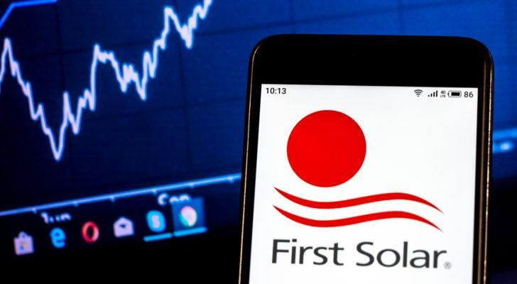 First Solar (FSLR) logo on smartphone in front of computer screen with graphs