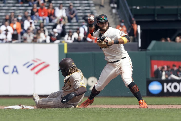 San Francisco Giants shortstop Brandon Crawford, right, throws to first base after forcing San Diego Padres' Fernando Tatis Jr. out at second base during the fifth inning of a baseball game in San Francisco, Thursday, Sept. 16, 2021. (AP Photo/Jeff Chiu)