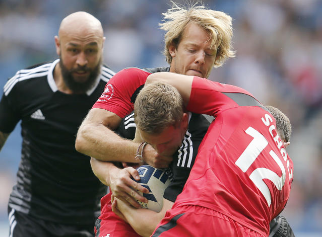 New Zealand's Scott Curry, center, and D J Forbes, left, challenge for the ball with Canada's Mike Scholz , right, and Harry Jones during the Rugby Sevens Pool A match 1 between New Zealand and Canada at the Ibrox stadium during the Commonwealth Games 2014 in Glasgow, Scotland, Saturday July 26, 2014. (AP Photo/Frank Augstein)