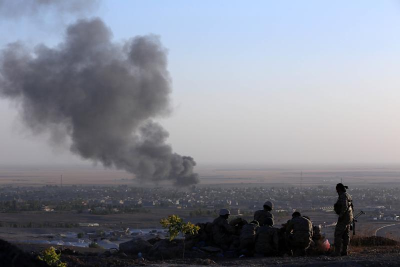 Iraqi Kurdish Peshmerga fighters look on as smoke billows from the town Makhmur, Iraq during clashes with Islamic State militants on August 9, 2014 (AFP Photo/Safin Hamed)