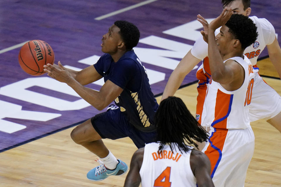 Oral Roberts guard Max Abmas, left, drives to the basket ahead of Florida guard Noah Locke, right, during the first half of a college basketball game in the second round of the NCAA tournament at Indiana Farmers Coliseum, Sunday, March 21, 2021 in Indianapolis. (AP Photo/AJ Mast)
