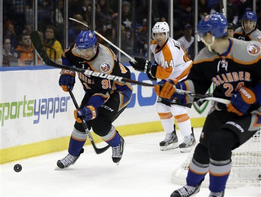 New York Islanders' John Tavares, left, moves the puck during the second period of the NHL hockey game against the Philadelphia Flyers Monday, Feb. 18, 2013, in Uniondale, N.Y. (AP Photo/Seth Wenig)