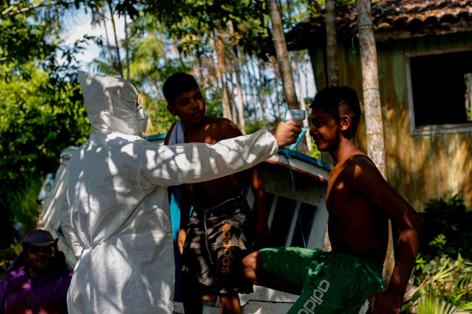 A Health worker measures the temperature of riverside residents at the Pindobal community in the Igarape-Miri municipality, lower Tocantins region, northeast of Para state, Brazil on October 28, 2020. - The state of Para health department prepares to have a second coronavirus wave and increased the measures to prevent the spread of the COVID-19. Health authorities confirmed on Wednesday 956 more cases of Covid-19 and three deaths raisinfg the toll to 251,292 cases and 6,736 deaths in the state. (Photo by TARSO SARRAF / AFP) (Photo by TARSO SARRAF/AFP via Getty Images)