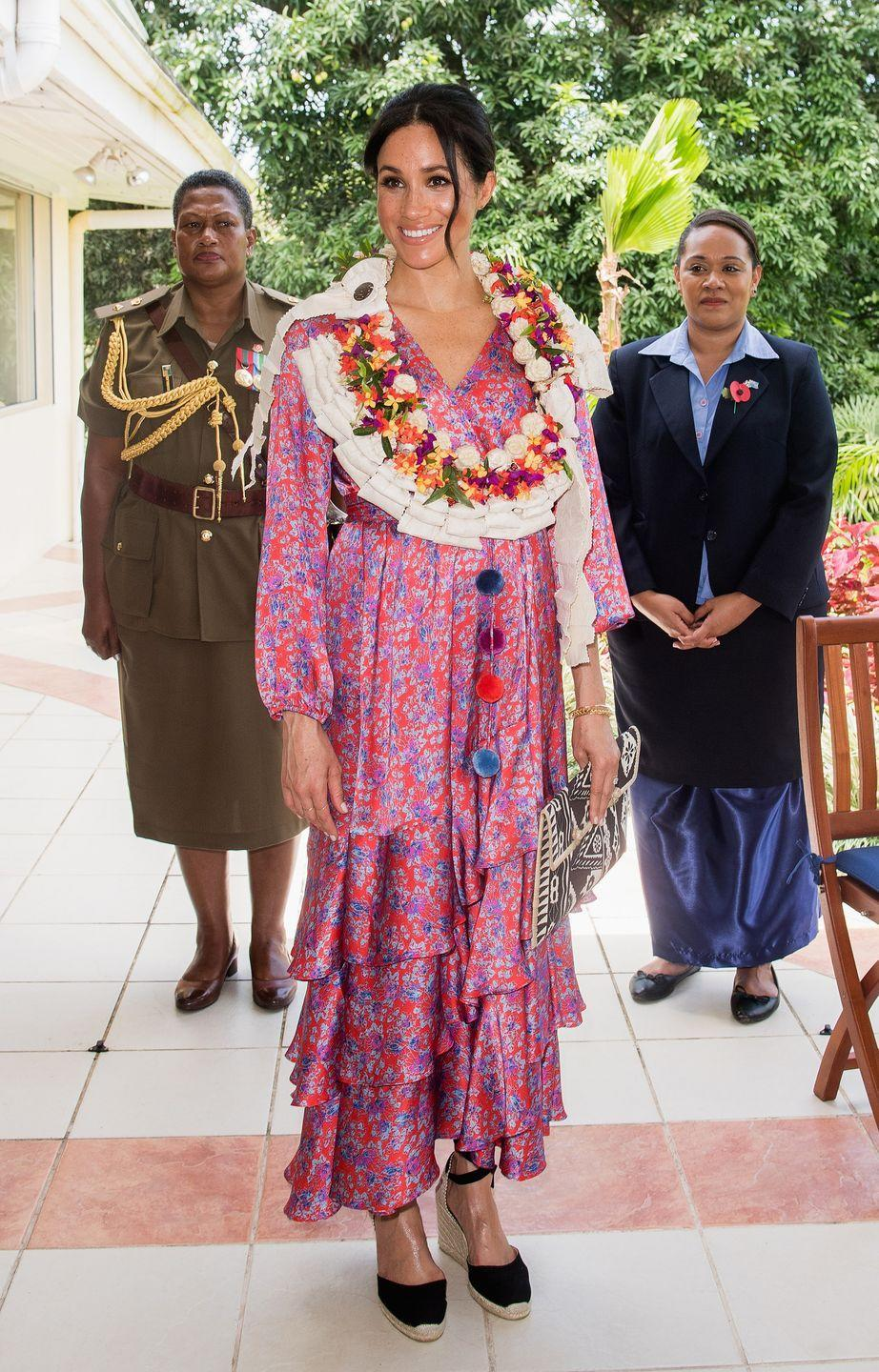 """<p>Meghan stepped out in Fiji <a href=""""https://www.townandcountrymag.com/society/tradition/a24112168/meghan-markle-style-pink-dress-figue-fiji/"""" rel=""""nofollow noopener"""" target=""""_blank"""" data-ylk=""""slk:wearing a printed pink dress"""" class=""""link rapid-noclick-resp"""">wearing a printed pink dress</a> by Figue. The Duchess was given <a href=""""https://www.townandcountrymag.com/society/tradition/g24109428/prince-harry-meghan-markle-fiji-royal-tour-day-2-photos/"""" rel=""""nofollow noopener"""" target=""""_blank"""" data-ylk=""""slk:a floral garland"""" class=""""link rapid-noclick-resp"""">a floral garland</a> during the visit. </p>"""