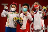 From left: Silver medallist India's Chanu Saikhom Mirabai, gold medallist China's Hou Zhihui and bronze medallist Indonesia's Windy Cantika Aisah celebrate their succes inteh women's 49kg weightlifting on Saturday at te Tokyo International Forum