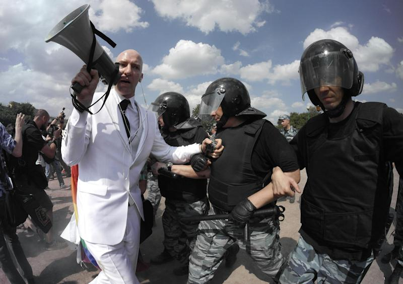 Riot police (OMON) officers detain gay rights activist Jury Gavrikov during an authorized gay rights rally in St.Petersburg, Russia, Saturday, June 29, 2013. Police detained several gay activists, who were outnumbered by the protesters. Dozens of gay activists had to be protected by police as they gathered for the parade, which proceeded with official approval despite recently passed legislation targeting gays. (AP Photo/Dmitry Lovetsky)