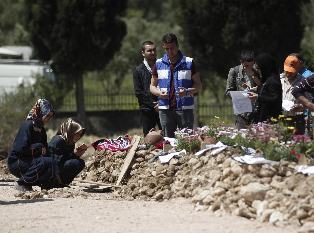 People mourn at graves for miners who died in Tuesday's mine disaster, at a cemetery in Soma, a district in Turkey's western province of Manisa May 18, 2014. Turkish police have detained 18 people, including mining company executives and personnel, as part of an investigation into last week's mine disaster, CNN Turk and other broadcasters reported on Sunday. The rescue operation ended on Saturday after the bodies of the last two workers were carried out, bringing the death toll in Turkey's worst industrial accident to 301. REUTERS/Osman Orsal (TURKEY - Tags: DISASTER)