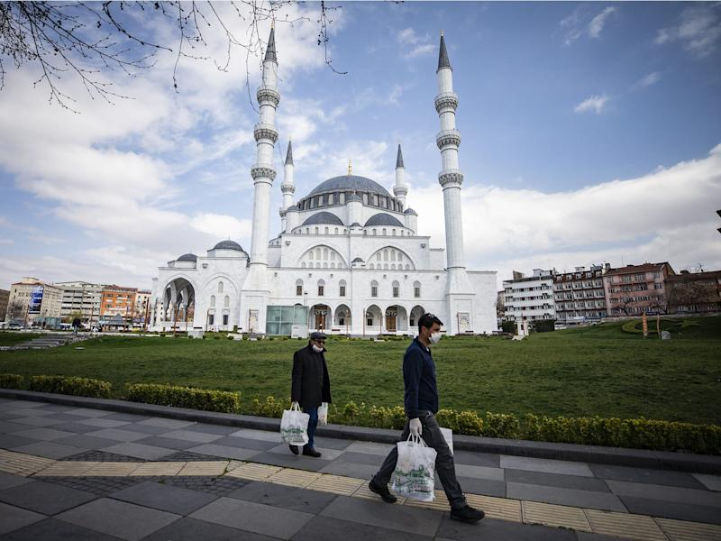 People wearing mask walk in front of empty Melike Hatun Mosque as people are staying home within measures taken against the coronavirus pandemic in Ankara, Turkey on April 6.