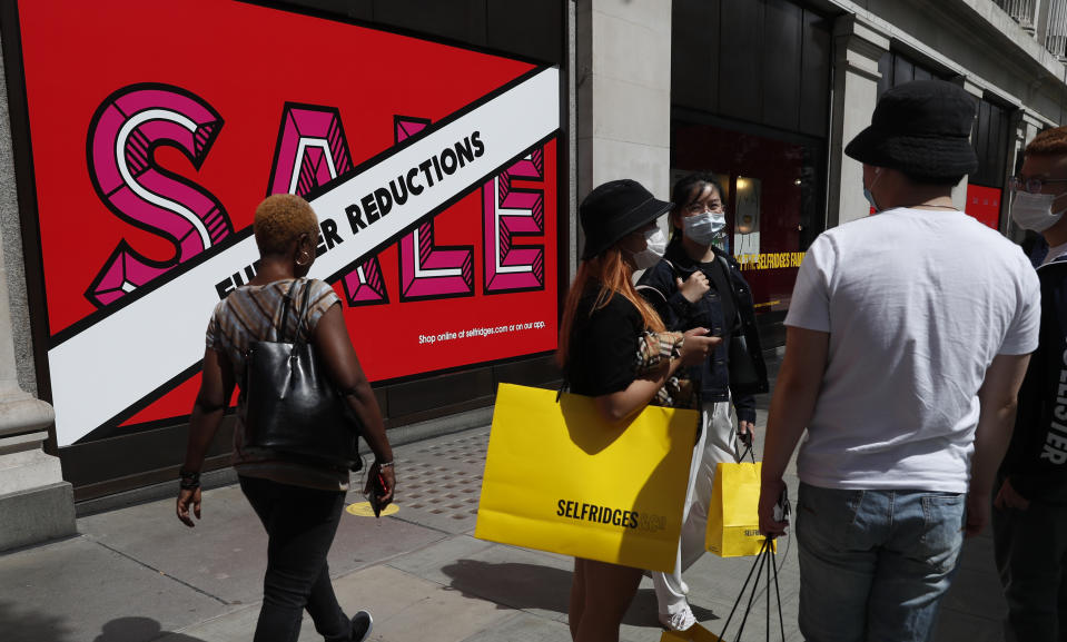 "Shoppers stand in front of a large department store wearing masks in London, Thursday, July 23, 2020. Making masks mandatory in shops is ""the right thing to do,"" Britain's Prime Minister Boris Johnson said Thursday, a day before new rules were set to come into force in England. (AP Photo/Alastair Grant)"