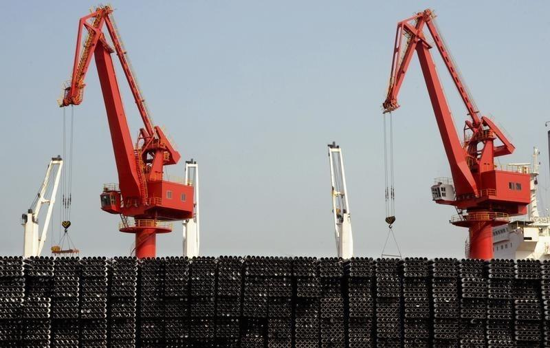 Piles of steel pipes to be exported are seen in front of cranes at a port in Lianyungang
