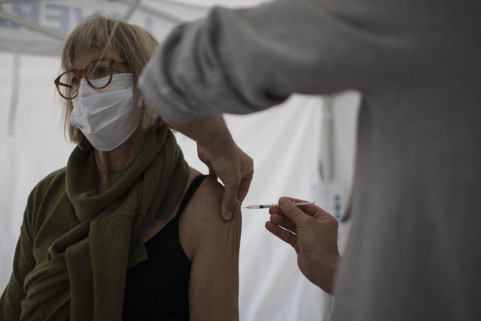 A woman receives the Pfizer COVID-19 vaccine at the Laveran Military Hospital in Marseille, southern France, Wednesday, April 7, 2021. Seven military hospitals also opened vaccination centers on Tuesday, operated by military and civilian staff, in an effort to inject up to 50,000 doses per week, the defense ministry said. (AP Photo/Daniel Cole)